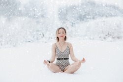 Pretty woman wearing swimsuit practising cold therapy in a beautiful freezing winter nature surrounded by snow. Healthy cold exposure method.