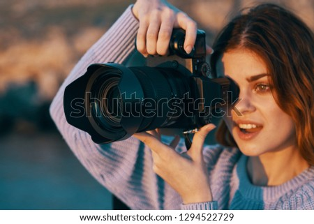 Pretty woman with a camera takes pictures of nature