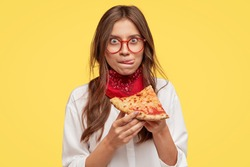 Pretty woman with appealing appearance, licks lips, holds slice of tasty pizza, being hungry, wants to eat, enjoys taste, has good appetite, isolated over yellow studio wall. People and snack concept
