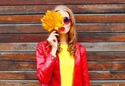 pretty woman with autumn yellow maple leaves over wooden background
