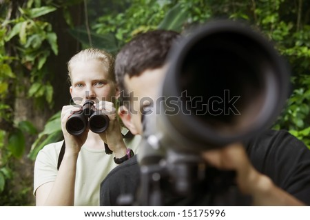 Pretty Woman with Binoculars and Man with Telescope in Rain Forest Jungle