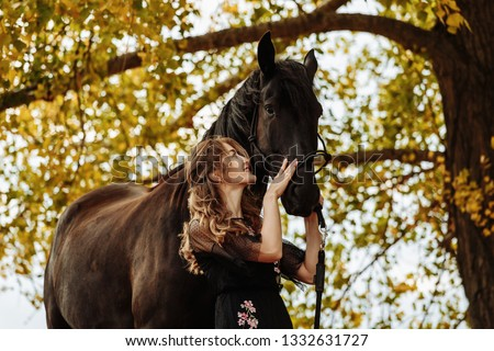 Stock Photo pretty woman with black horse in autumnal nature. Fashion photoshoot