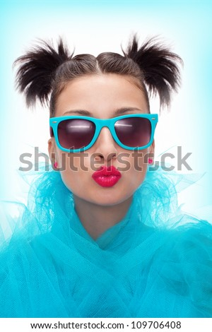 pretty woman with blue eyeglasses is blowing a kiss