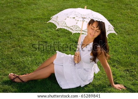 Pretty woman with closed eyes enjoying summertime on the green lawn