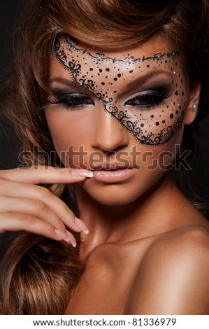 Pretty woman with creative makeup , mask on women\'s face