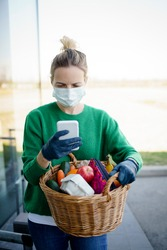 Pretty woman with face mask and green pullover and black gloves makes a phone call after shopping and is holding her shopping basket