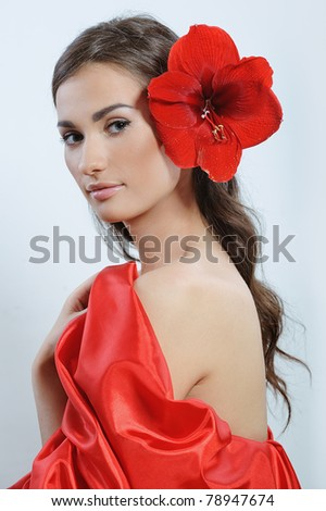 pretty woman with fresh red flower in the hear after spa procedures
