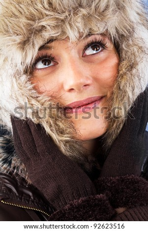 Pretty woman with fur hat looking up with her beautiful eyes. Studio shot as a winter portrait. - stock photo