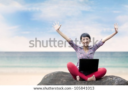 Pretty woman with laptop sitting on the stone under blue sky, shot at the beach