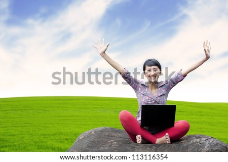 Pretty woman with laptop sitting on the stone under clear sky
