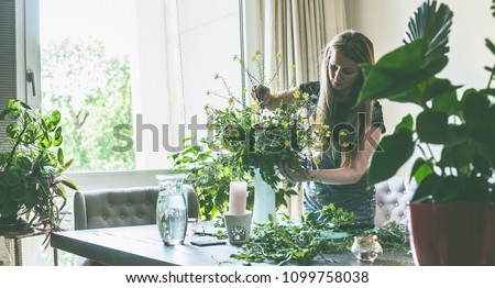Pretty woman with long hair arranging wild flowers bunch in vase on table in living room at window with sunset light. Home lifestyle and decor ideas