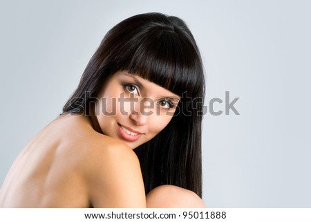 pretty woman with long straight black hair looking at camera, isolated on gray background
