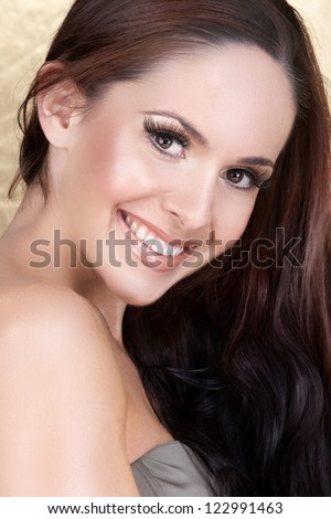 pretty woman with long straight brown hair with a happy smile on studio background