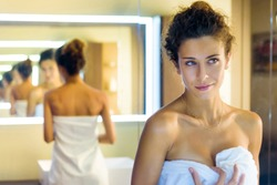 Pretty woman wrapped in a white towel admiring herself in a bathroom mirror with the reflection repeated multiple times in a receding perspective alternating rear and frontal views