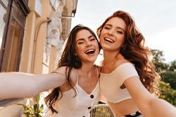 Pretty women have fun and take selfie on great terrace. Cute ladies in white summer clothes hugging and posing for camera