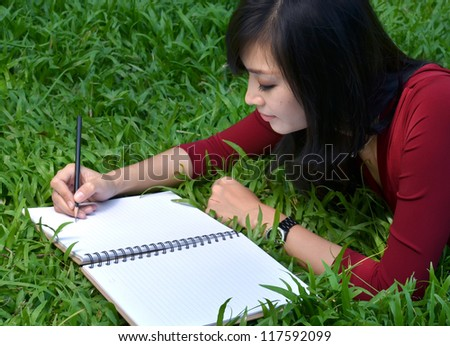 pretty women lying on green grass and writing book