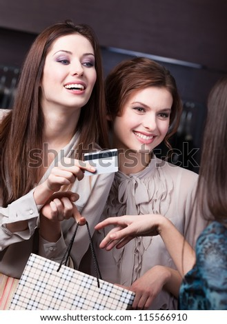 Pretty women settles an account with credit card at the store
