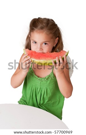 Pretty 5 year old girl eating watermelon at white table on a white background.