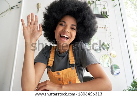 Pretty young African American mixed race hipster vlogger woman with Afro hair waving hand looking at webcam talking to camera sits at cafe table video calling, recording blog, headshot portrait.