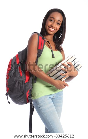 Pretty young African American teenager student girl with big smile wearing red backpack and holding school books. She has long black hair and wearing green vest and blue jeans.