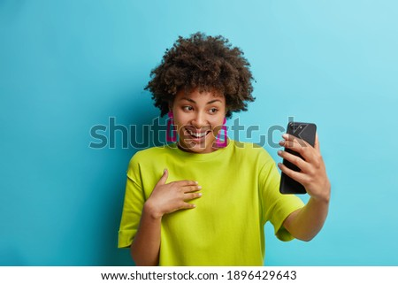 Pretty young African American woman holds modern mobile phone in front of herself has online conference makes video call connected to wireless internet enjoys positive talk wears green t shirt Photo stock ©