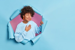 Pretty young African American woman presses hand to chest feels thankful expresses gratitude says thank you very much looks pleasantly aside dressed in casual jumper poses through hole of paper wall