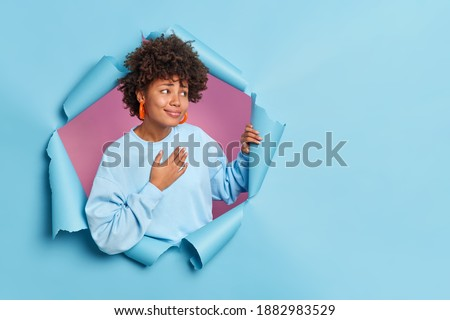 Pretty young African American woman presses hand to chest feels thankful expresses gratitude says thank you very much looks pleasantly aside dressed in casual jumper poses through hole of paper wall Photo stock ©