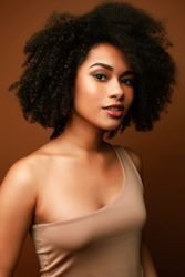 pretty young african american woman with curly hair posing cheerful gesturing on brown background, lifestyle people concept