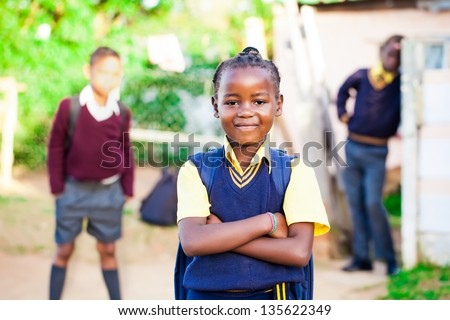 pretty young african girl standing proud in her yellow and blue school uniform with siblings watching over her.