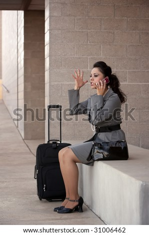 Pretty young angry Hispanic woman with roller suitcase talking on cell phone
