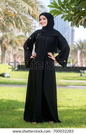 Pretty young arab woman in abaya. woman standing in the city park. Full length view.