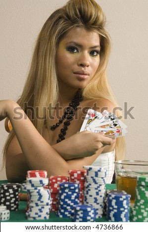 Pretty young Asian-American woman with blonde hair shows hand of cards by stacks of poker chips and drink