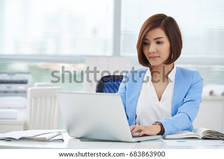 Pretty young Asian business woman working on computer in her office #683863900