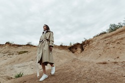 Pretty young asian girl going down from the sand quarry in a beige trench coat.