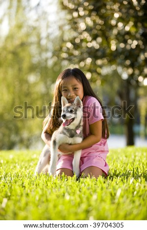 Pretty young Asian girl hugging Alaskan Klee Kai puppy sitting on grass