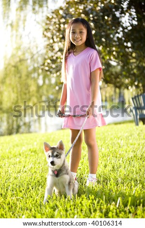 Pretty young Asian girl walking Alaskan Klee Kai puppy on leash on grass