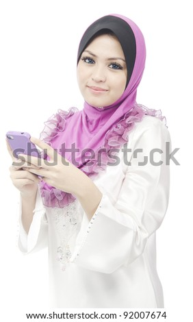 Pretty young Asian Muslim woman hold her phone while dialing number to make voice call.