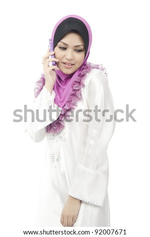 Pretty young Asian Muslim woman hold her phone while looking at bottom.