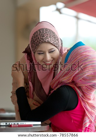Pretty young Asian Muslim woman meeting friend at coffee shop