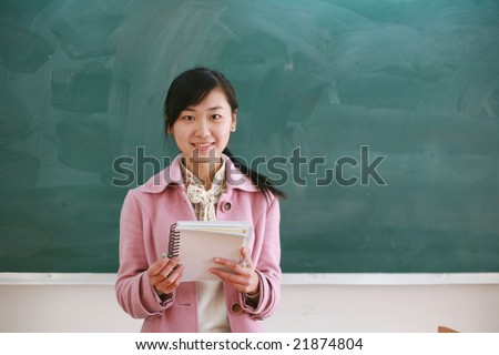 Pretty young asian teacher in front of a blackboard