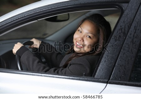 Pretty young asian woman driving her new car, smiling
