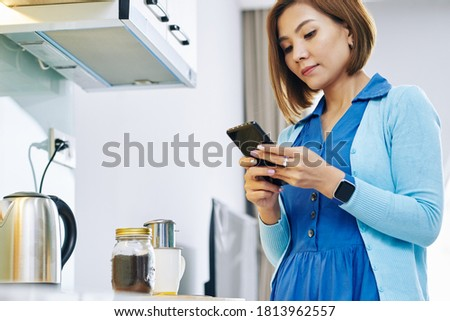 Pretty young Asian woman waiting for dripping coffee on kitchen counter and answering text messages on her smartphone stock photo