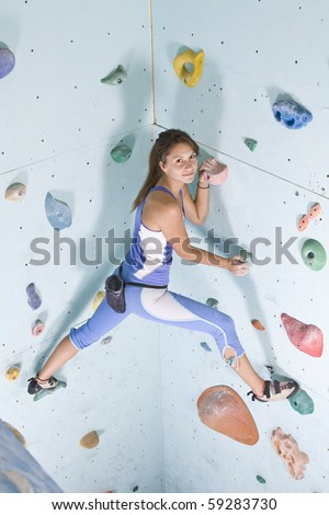 Pretty, young, athletic girl climbing on an indoor rock-climbing wall - stock photo