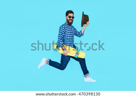 Stock Photo Pretty young bearded man jumping with yellow skateboard against the colorful wall. Hipster in motion on blue background