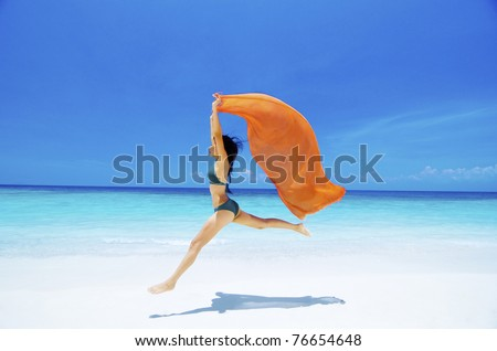 stock photo : Pretty young bikini girl is jumping up in the air at the beach