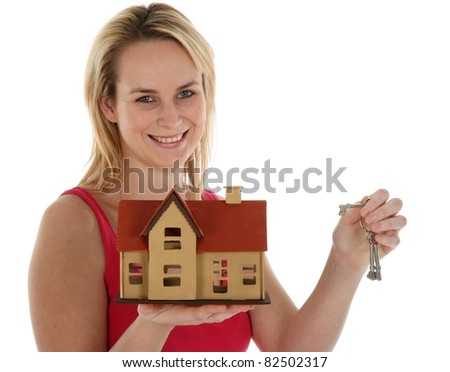 Pretty young blond estate agent sales lady holding out a model house and keys