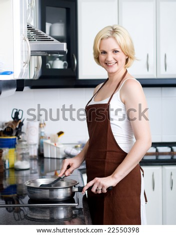 Pretty young blond woman cooks dinner in her kitchen