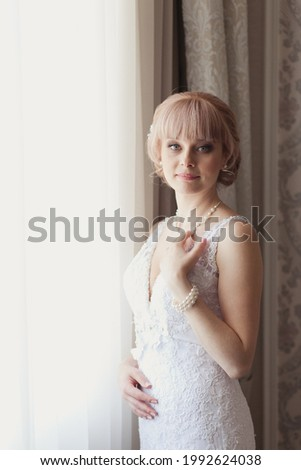 Pretty young Bride in elegant wedding dress near a window. Blonde-haired woman with wedding hair-style in royal room of hotel. Bride's morning in luxury interior. Wedding day ceremony