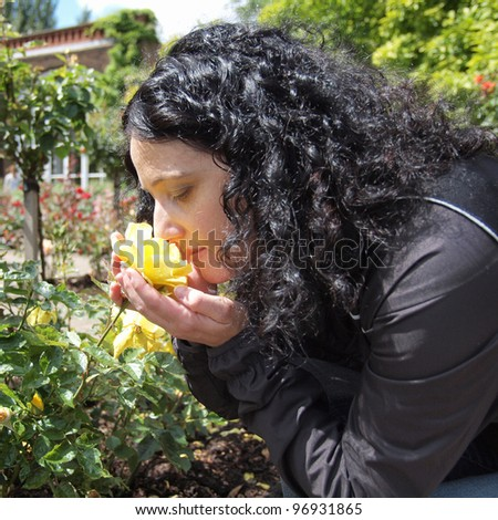 Pretty young brunette girl woman female smelling roses in a park - stock photo