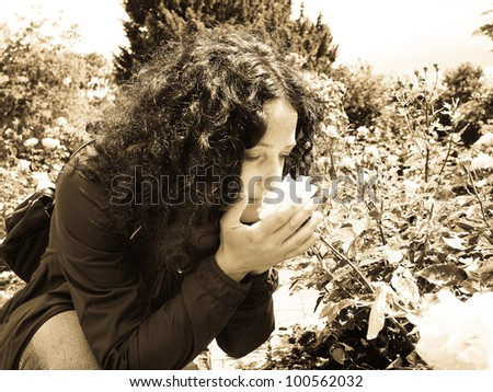 Pretty young brunette girl woman female smelling roses in the garden